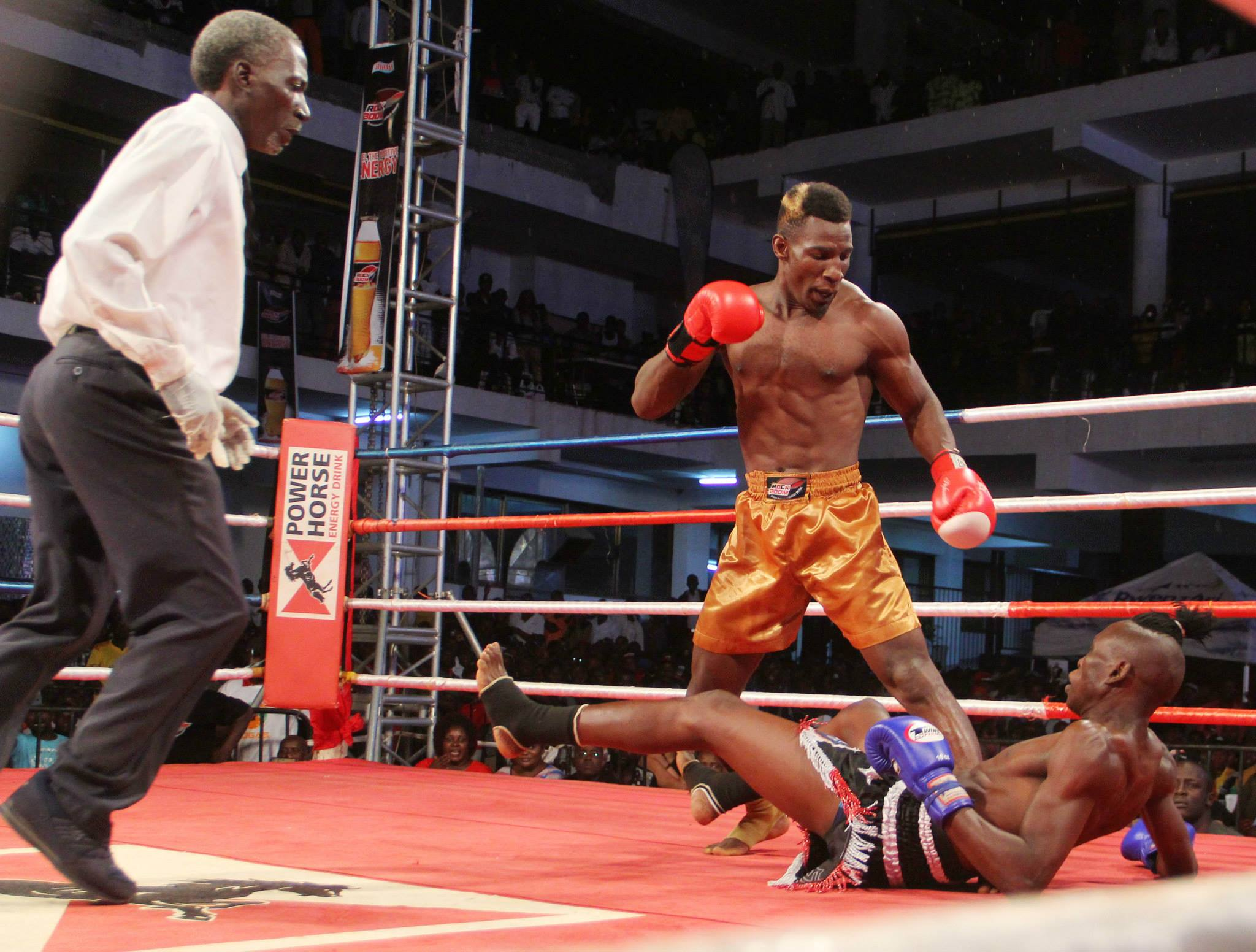 Golola follows on the heavy puch that sends Mugula to th turf to 'finish him off'