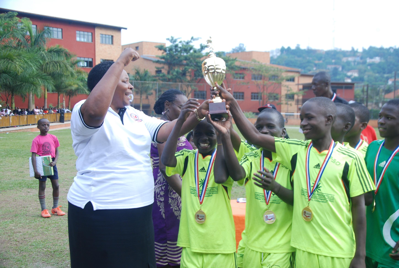Kampala Parents School Principal handing over a trophy to Muto Primary School