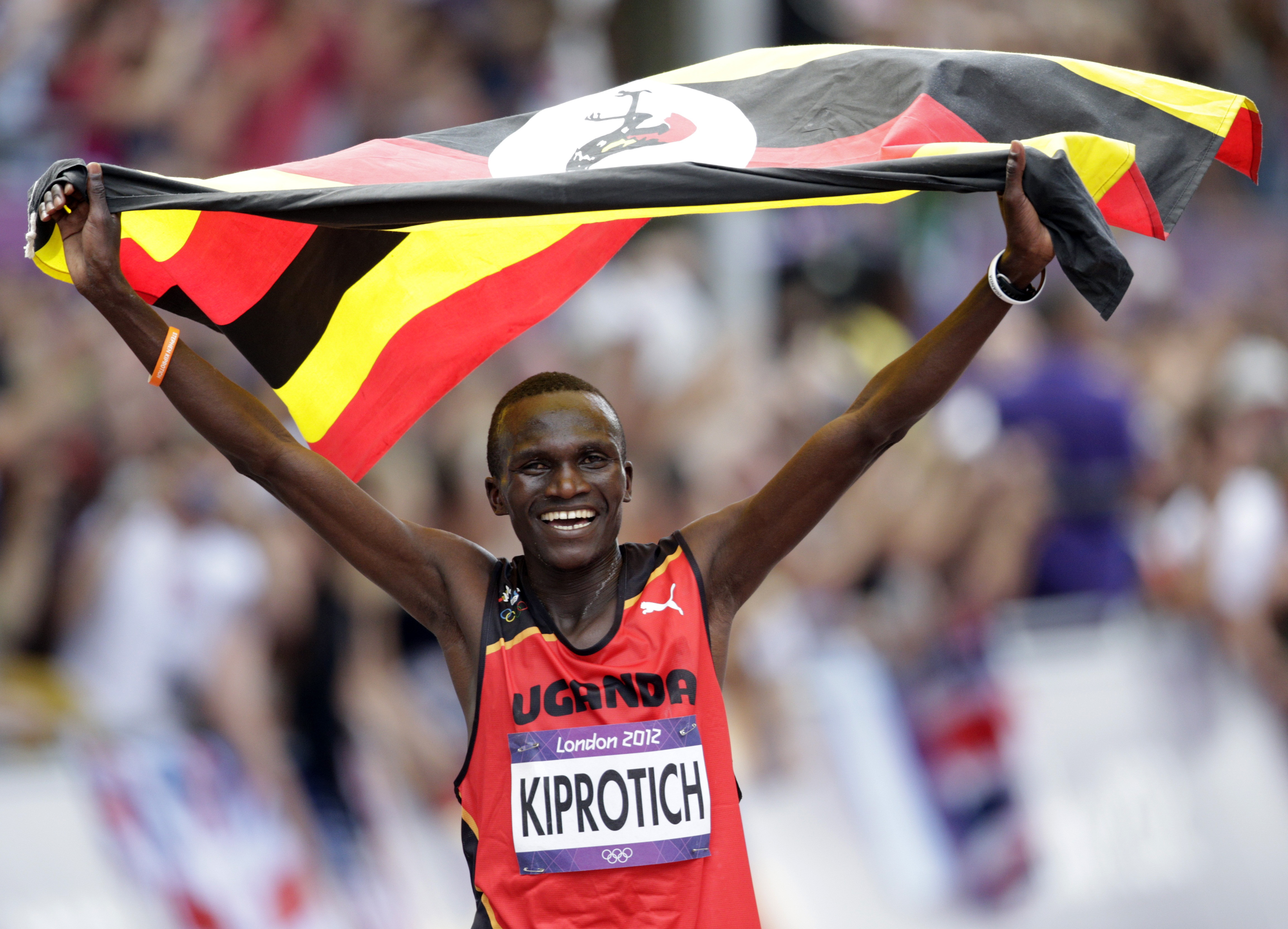 Uganda's Stephen Kiprotich celebrates with his national flag after winning the men's marathon in the London 2012 Olympic Games at The Mall August 12, 2012. REUTERS/Max Rossi (BRITAIN - Tags: SPORT ATHLETICS OLYMPICS)