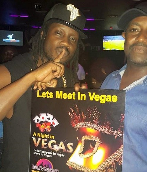 Bebe Cool holds up a poster  for a night in vegas