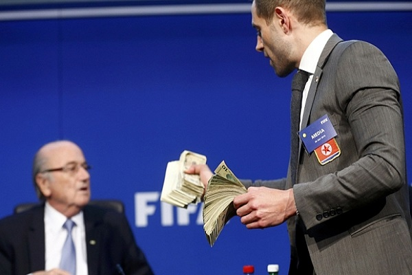 British comedian known as Lee Nelson holds banknotes in front of FIFA President Sepp Blatter (L)  before he threw them at him